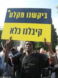 פליט נושא שלט במצעד זכןיות האדם