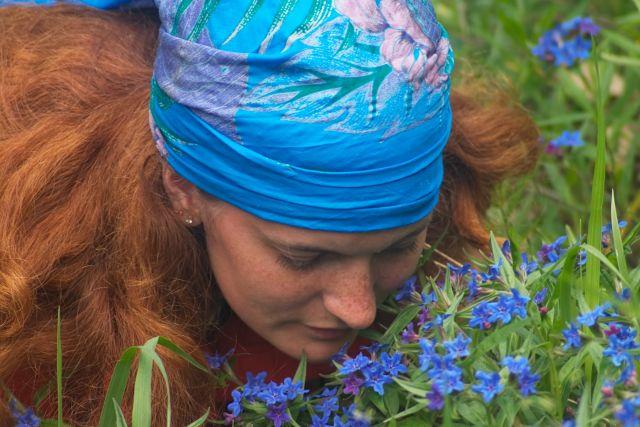 בחורה מריחה פרחים כחולים