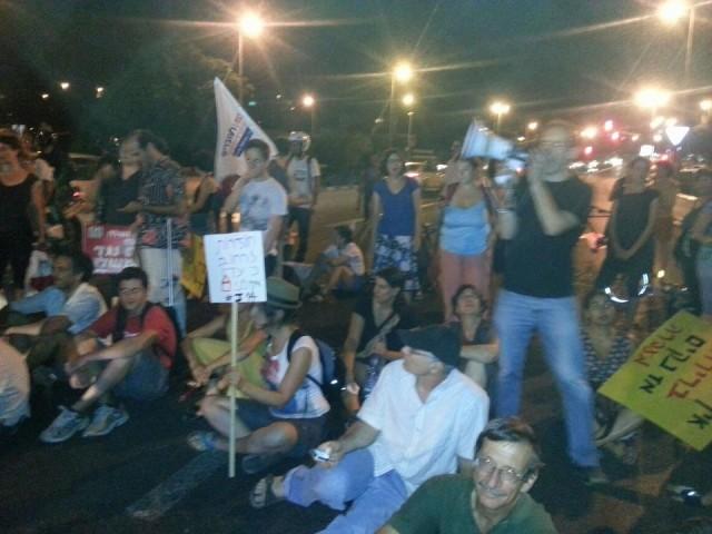 רגע חזק של סולידריות בצעדת הדיור הציבורי בירושלים. פעיל נעצר. כל הפעילים יושבים על הכביש ותובעים את שחרורו