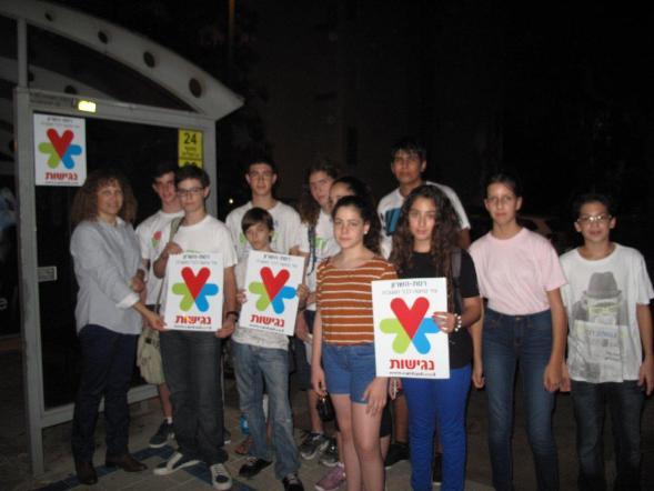 """סגנית ראש העירייה שירה אבין ובני נוער מתנדבים בתחנת אוטובוס שהונגשה לנכים (צילום: דוברות רמה""""ש)"""