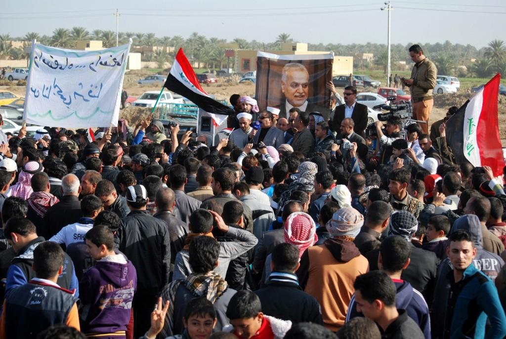 מפגינים סונים ליד העיר רמאדי שבמחוז אל-אנבאר מוחים על מדיניות ממשלת אל-מאלכּי ומניפים את תמונתו של סגן הנשיא הגולה, הסוני טארק אל-האשמי (צילום: AFP PHOTO/STR)