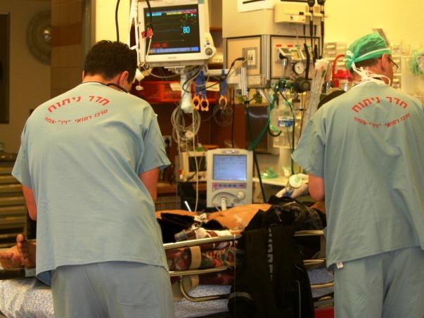 רופאי המרכז הרפואי זיו מטפלים בפצוע סורי בחדר הטראומה (צילום: בית החולים)