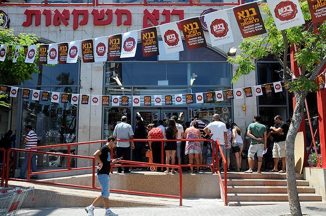 תושבים להוטים בחום הלוהט ממתינים לפתיחת החנות (צילום: יולה זובריצקי)