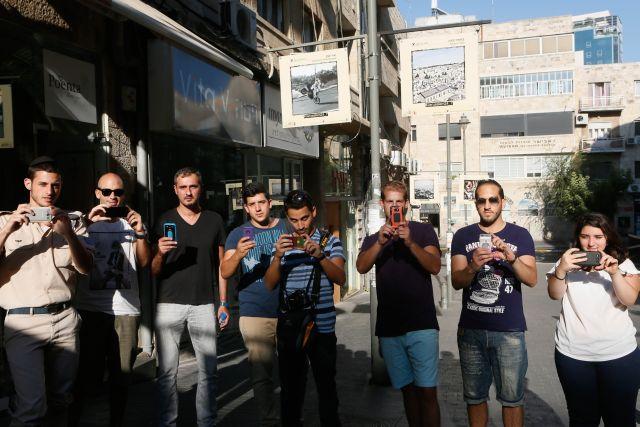 """צלמי האינסטגרם הירושלמים, על רקע תמונותיהם במדרחוב ש""""ץ. (צילום: פלאש 90)"""