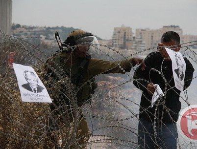 חייל מורה לפלסטיני להסיר את תמונות מנדלה (צילום: סוכנות מען)