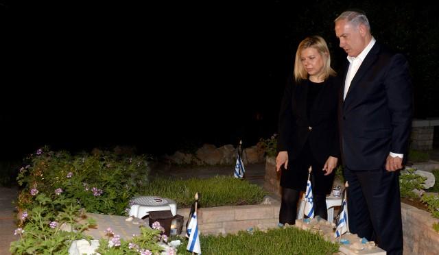 """ראש הממשלה בנימין נתניהו ורעייתו שרה, על קברו של יוני נתניהו ז""""ל, ביום חמישי בערב. (צילום: חיים צח/לע""""מ)"""