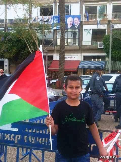 ילד נושא דגל פלסטין בכיכר. מעליו מציצים נתניהו וליברמן בכרזת בחירות (צילומים: ציפי מנשה)