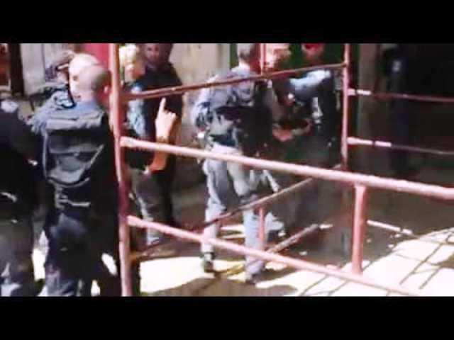 השוטר הזועם נהדף בידי חבריו (צילום מתוך הסרטון)