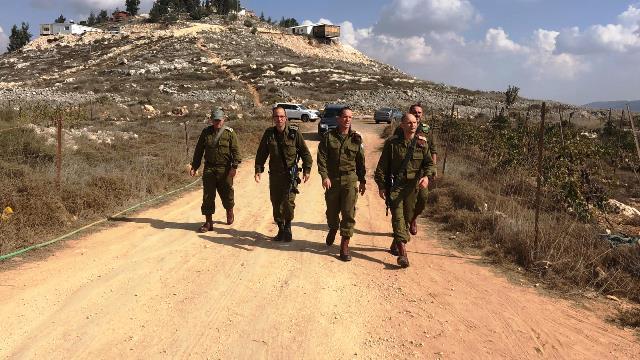 """סיור המפקדים על רקע הגבעה שהוכרזה כשטח צבאי סגור (צילום: דו""""צ)"""