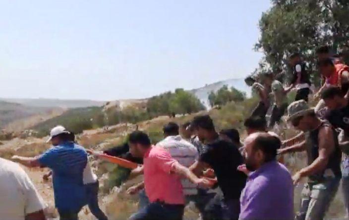פינוי הפצוע הפלסטיני  על ידי חבריו (צילום מתוך סרט הווידאו של מיכאלי)