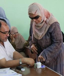בוחרת בקלפי בקהיר טובלת את אצבעה בדיו, כדי לחתום על טופס הבחירה שלה (Flickr/Nehal ElSherif)
