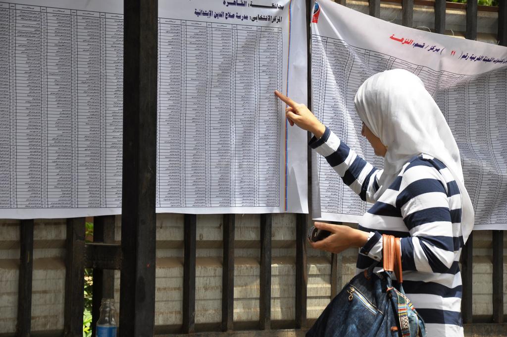 מצביעה מאתרת את שמה ברשימות הבוחרים התלויות מחוץ לקלפי בפרבר של קהיר (UN Women/Fatma El Zahraa Yassin)