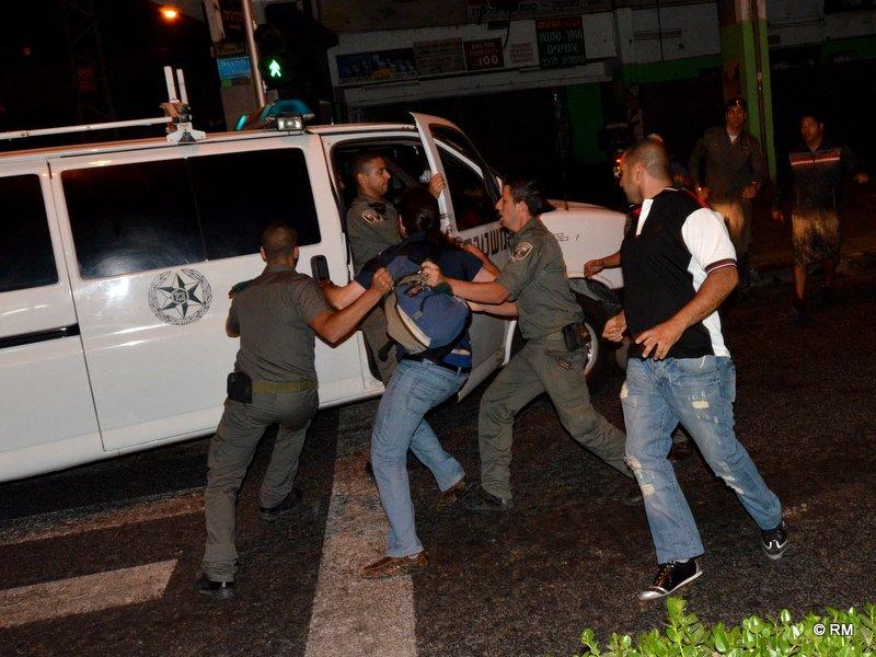שוטרים מפנים אדם שהותקף בידי המפגינים (צילום: רפי מיכאלי)
