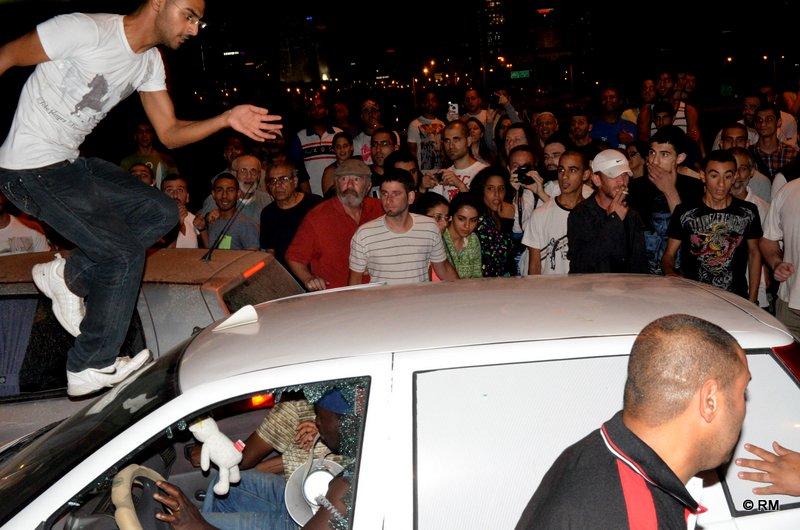 מפגינים מתנפלים על מכונית עם מהגרים ומנפצים שמשות לאחר ההפגנה בשוק תקווה (צילום: רפי מיכאלי)