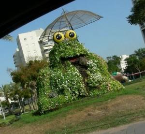 פסל חוצות באשדוד: צפרדע עם שמשיה - שלד רשת עם פרחי העונה. (צילום: רבקה יניב)