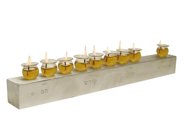 """חנוכית שמן בכלי זכוכית על בסיס אלומיניום מעובד ידנית. עיצוב: יוריני לסטודיו יויו32. מחיר: 1600 ש""""ח. צילום: צפריר קאשי"""