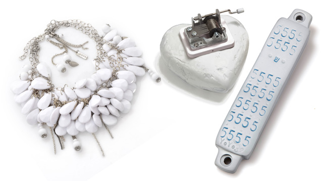 פריטים בעיצוב יוריני: מזוזה לבנה עם הטבעת המספר 5 למזל, מסדרת מזוזות נווה צדק; משקולת נייר שהיא תיבת נגינה. צילום: ירון וינברג; שרשרת לבנה. צילום: צפריר קאשי.