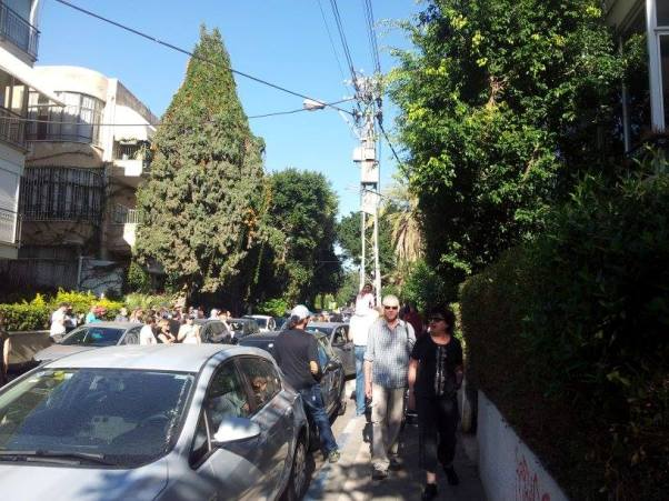 עשרות אנשים על המדרכות הצרות, ליד הבית וממול
