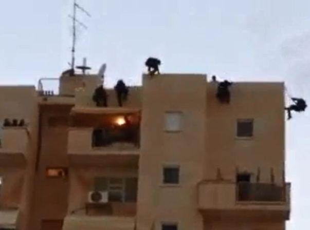 השוטרים משתלשלים מהגג ופורצים לדירה (משטרת ישראל)
