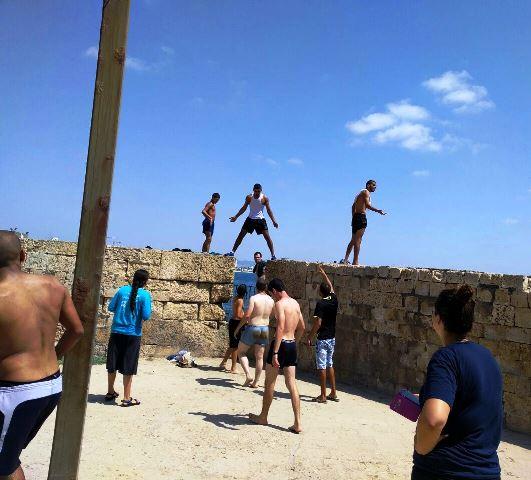 הצעירים היהודים והערבים מתווכחים על התור לקפיצה מהחומה (צילום באדיבות חוננו)