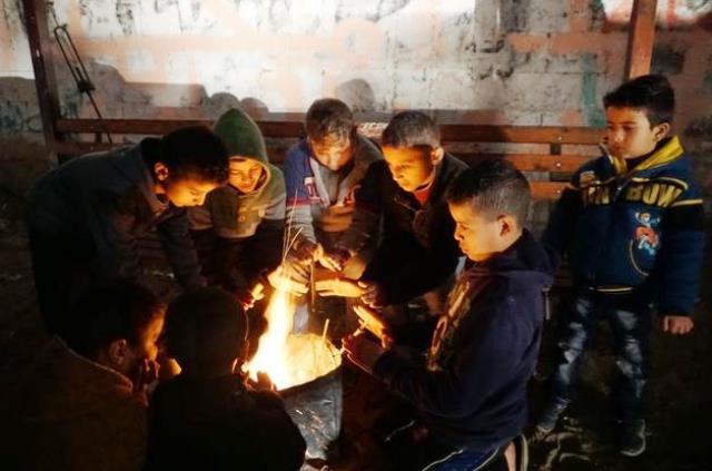 ילדים מצטופפים  ליד אש - ינואר 2017 (צילום ארכיון -  משרד האום לעניינים הומניטריים)