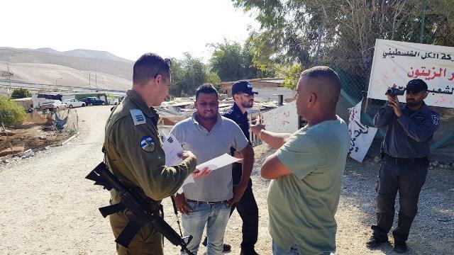 """קצין המנהל האזרחי מוסר לתושבים את צווי ההריסה (צילום: דובר צה""""ל)"""