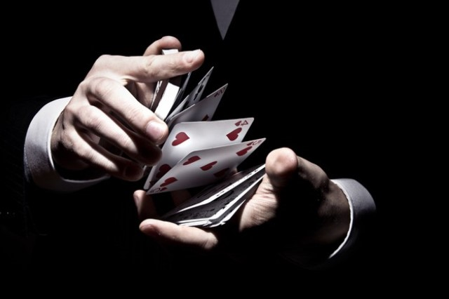 magician-shuffling-cards-cool-way-spotlight_181624-26713