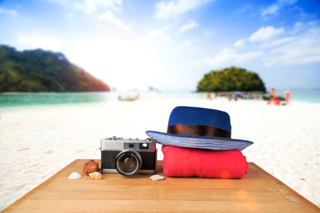 red-pink-tower-blue-hat-old-vintage-camera-shells-wooden-floor-sunshine-blue-sky-ocean-background_1421-402
