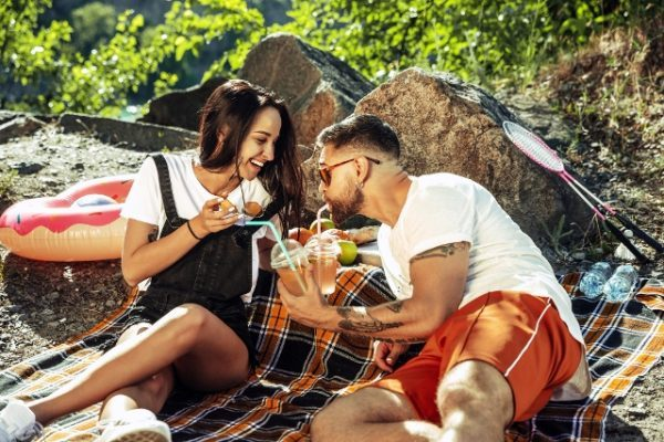 young-couple-having-picnic-riverside-sunny-day